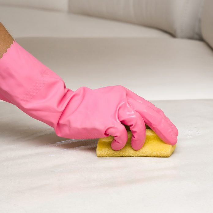 Cleaning-leather-sofa-with-sponge