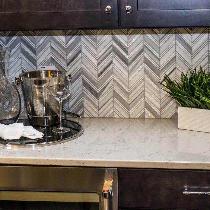 White-and-Gray-Chevron-backsplash-on-white-countertop-and-dark-cabinets