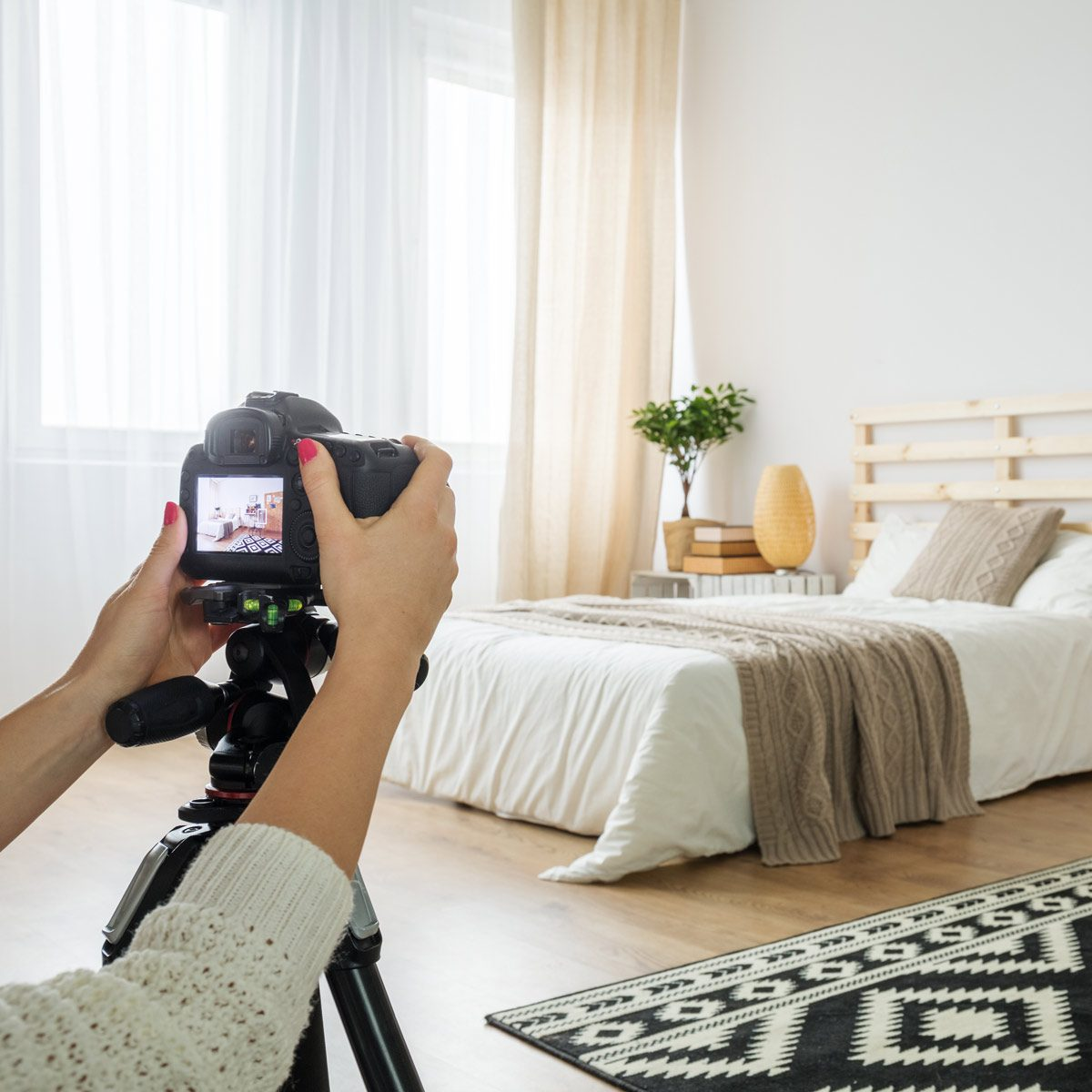 Woman takes a photo of a bedroom