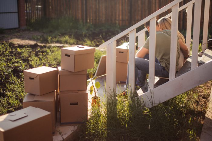 Family Outside House On Moving Day. cardboard boxes foreground near steps