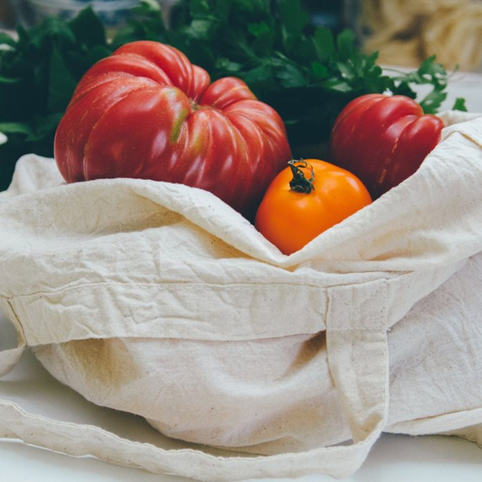 Reusable canvas grocery bag with red and yellow tomatoes and spinach.