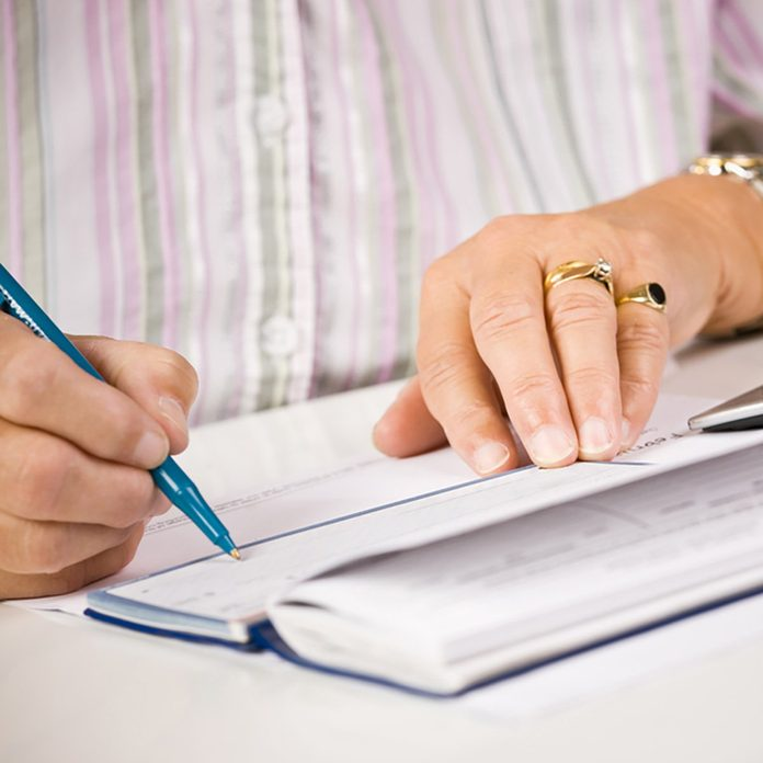 Senior woman writing check