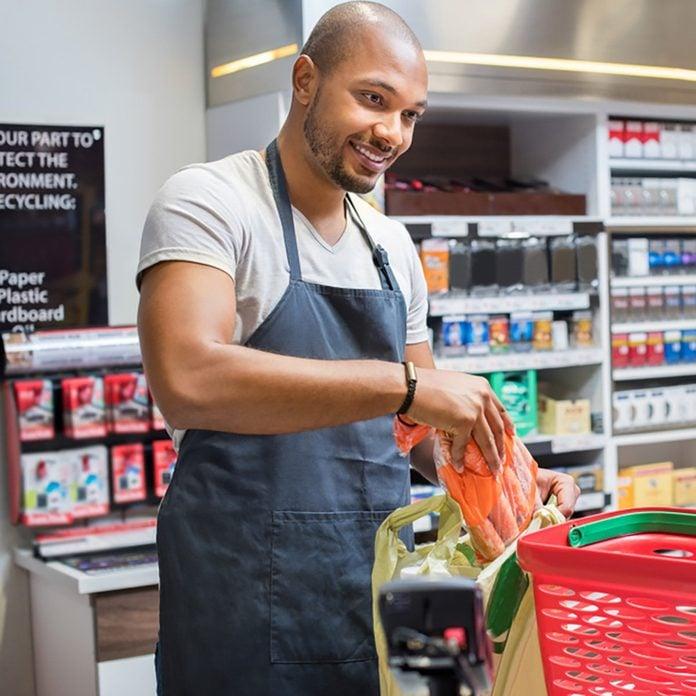 Smiling salesman putting vegetables in bag for customer after billing