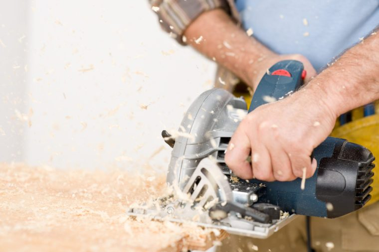 Home improvement - handyman cut wood with jigsaw in workshop