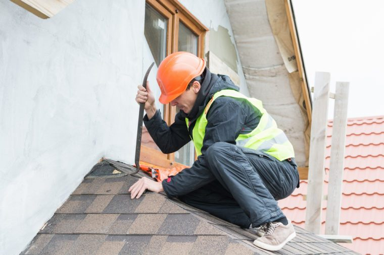 Roofer builder worker dismantling roof shingles