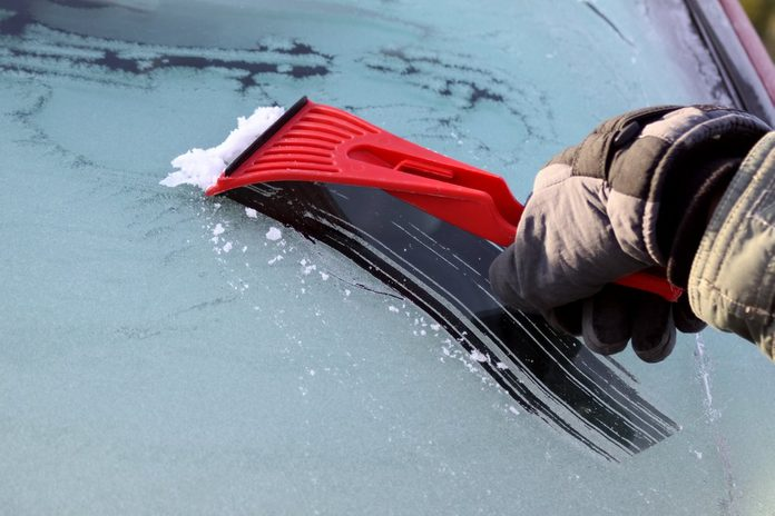 Scraping ice from the car window, with copy space