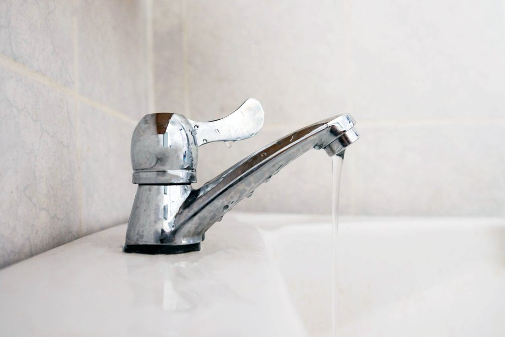 Close up dripping water drop of faucet in the bathroom , save water concept