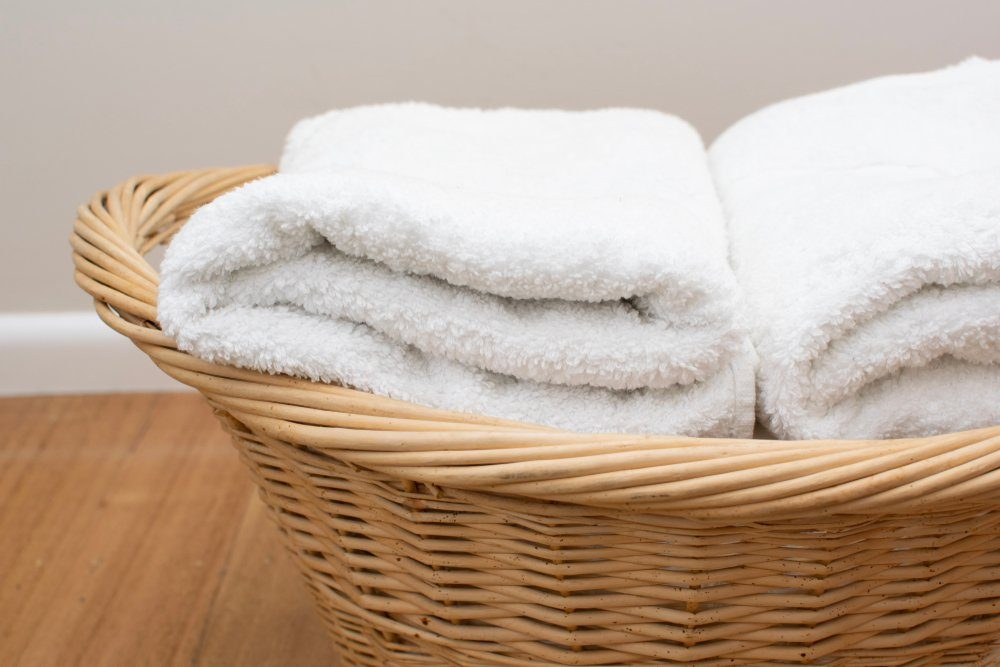 Soft white towels folded place in the rattan basket place on the wooden floor