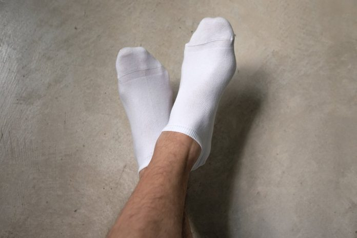 Man wearing socks crossing his legs. He is resting and moving his legs up