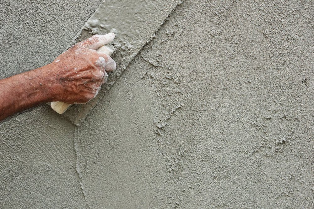 Asian male house-builder hand smoothing the mortar applied on an outdoor wall with a plastering trowel.