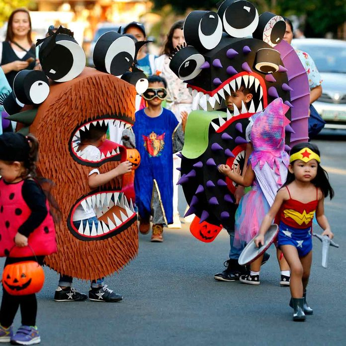 """Children, dressed in their colorful costumes make the rounds of the houses to solicit candies and sweets known as """"trick or treat"""" to celebrate Halloween, the eve of the observance of All Saints Day in suburban Makati city, east of Manila, Philippines"""