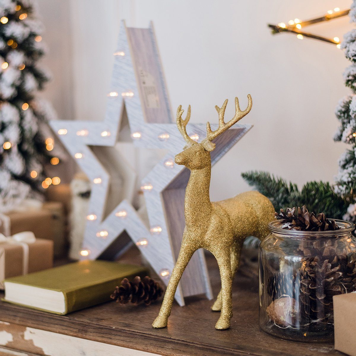 winter still life with Christmas decorations toy deer, star and gift boxes