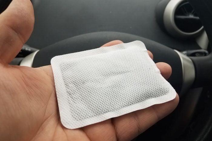 hand holding hand warmer in car