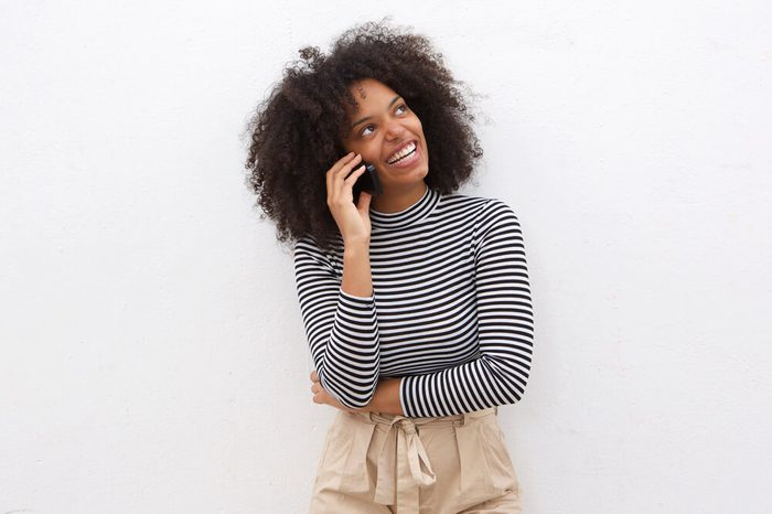 Portrait of happy black woman talking on mobile phone