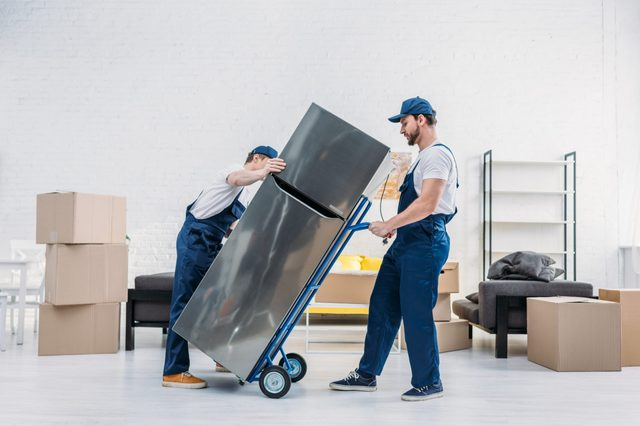 two movers in uniform using hand truck while transporting refrigerator in apartment
