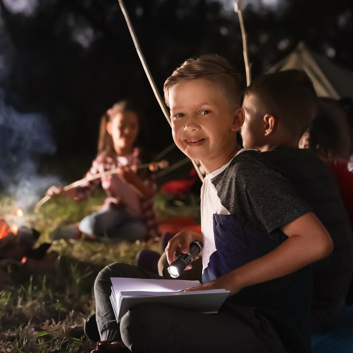 Little boy with book and flashlight near bonfire at night.