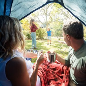 Rear view of couple having coffee and looking at kids playing outside the tent; Shutterstock ID 635870486; Job (TFH, TOH, RD, BNB, CWM, CM): TOH