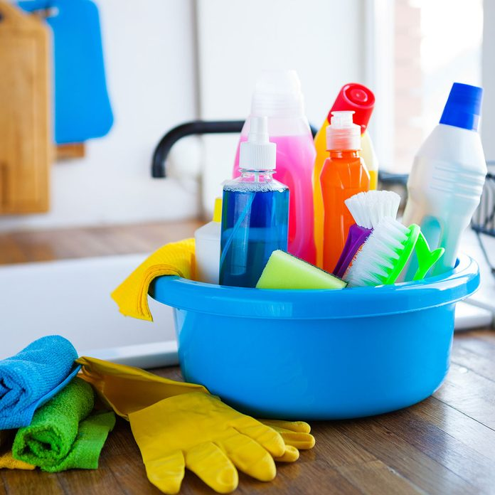 cleaning supplies in a bucket on a countertop