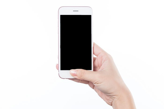 Concept of woman's hand holding a smartphone isolated on white background, clipping path, blank for webpage or message.