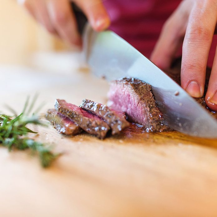 steak getting cut on a butcher block countertop