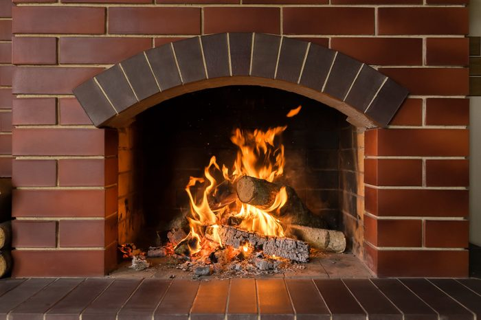 A brick fireplace in which a fire burns
