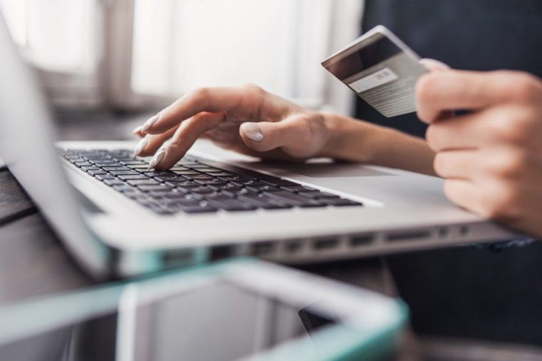 Hand holding credit card and using laptop. Online shopping concept