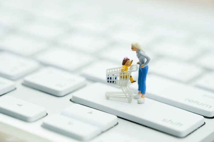 Miniature people: Shopper with shopping cart on keyboard using as background business online concept.