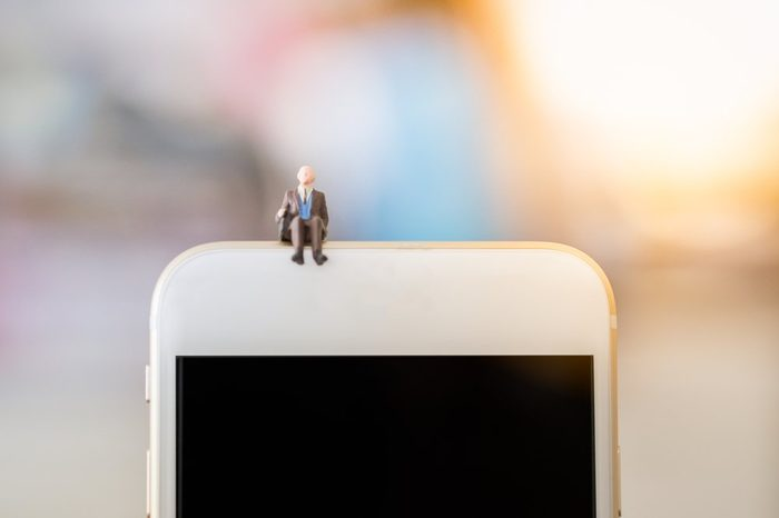 Business, technology concept. Businessman miniature tiny figure toy sit on the top of smart phone with copy space