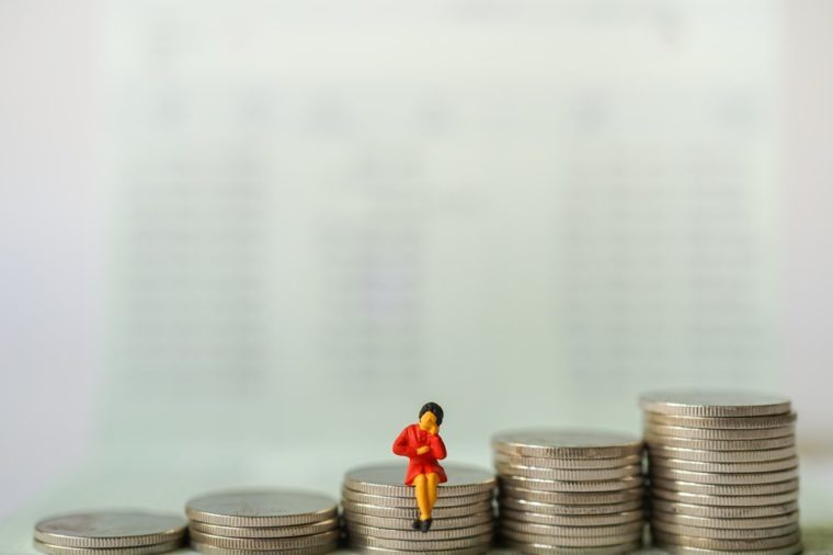 Miniature people : Business women sitting and thinking about business on stack of coins, e-commerce, online technology business concept