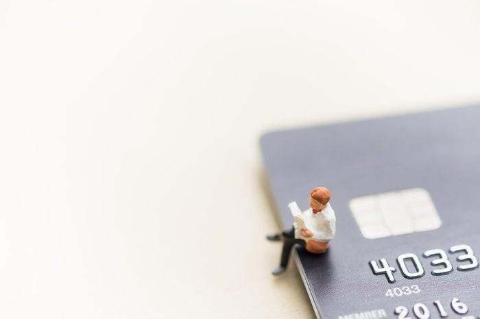 Finance, Business, Shopping and e-commerce concept. Close up of man miniature figure toy sit and read a book on stack of credit cards