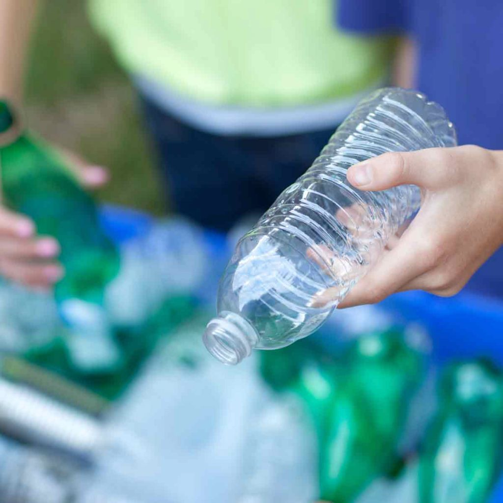 Caucasian-boy-and-girl-putting-clear-and-green-bottles-and-metal-cans-in-recycling-blue-bin-outside-in-yard
