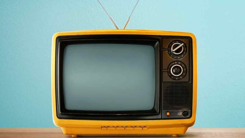 Yellow-Orange-color-old-vintage-retro-Television-on-wood-table-with-mint-blue-background