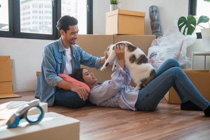 Young Asian couple or family feeling happy relaxing and play with their cat after moving to new house or apartment.