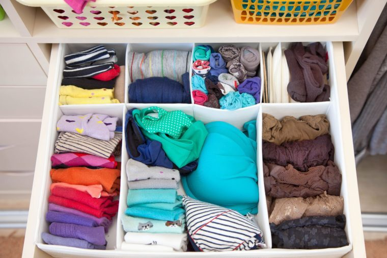 Women's clothing in the drawers of the wardrobe. Underwear, T-shirts and socks in the closet. Vertical storage.