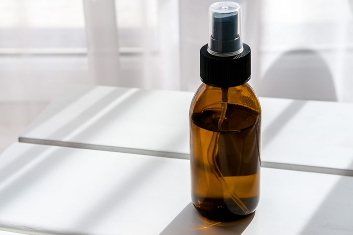 Glass brown spray bottle with organic cosmetics on white table. Direct light. Beauty blogging minimalism concept
