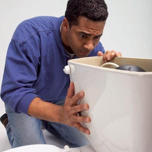 Man looking at a toilet