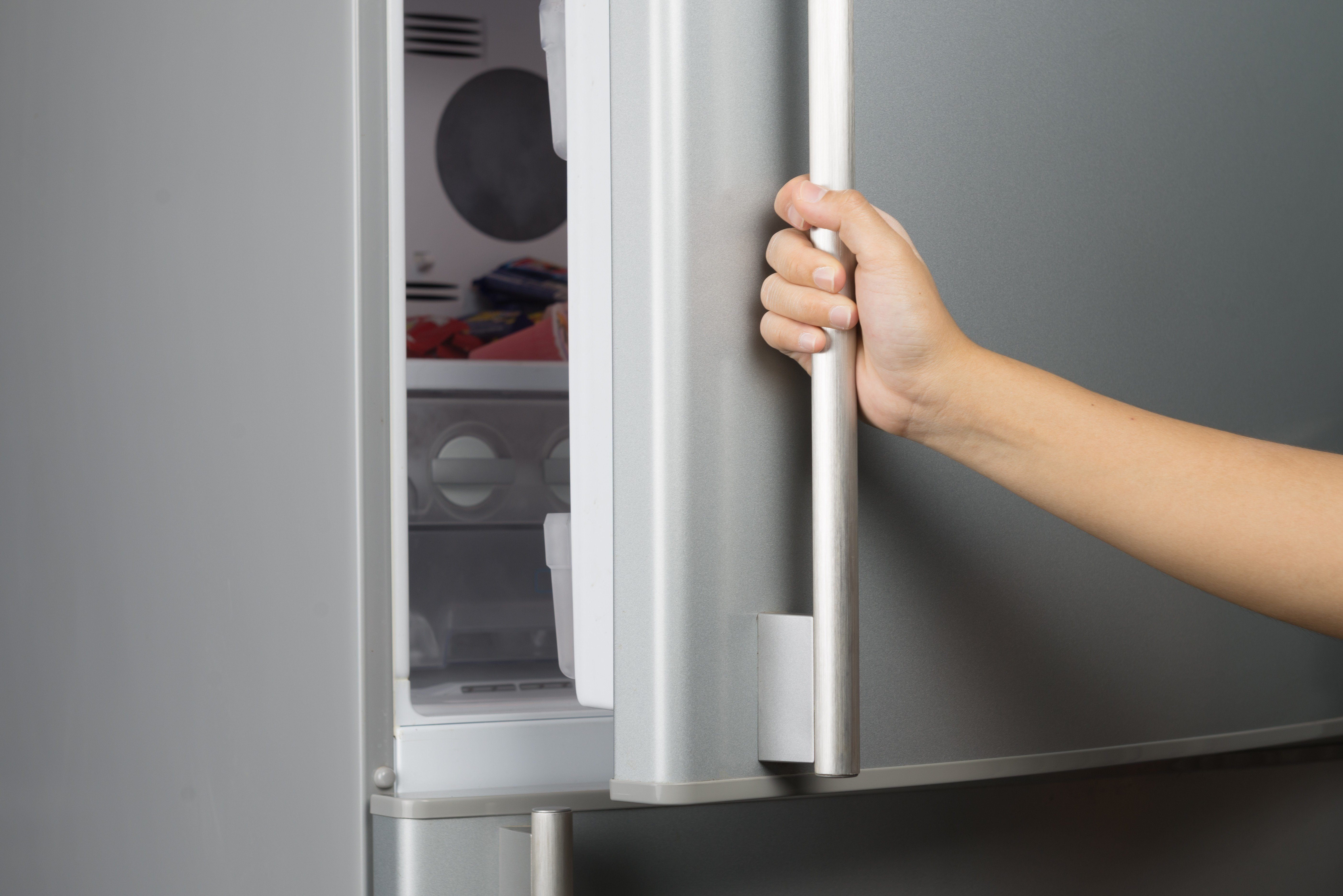 Hand of a woman is opening a refrigerator door