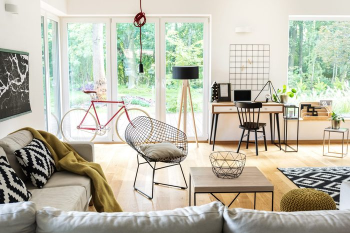 Red bike near the window in bright living room with black and white workspace and terrace view