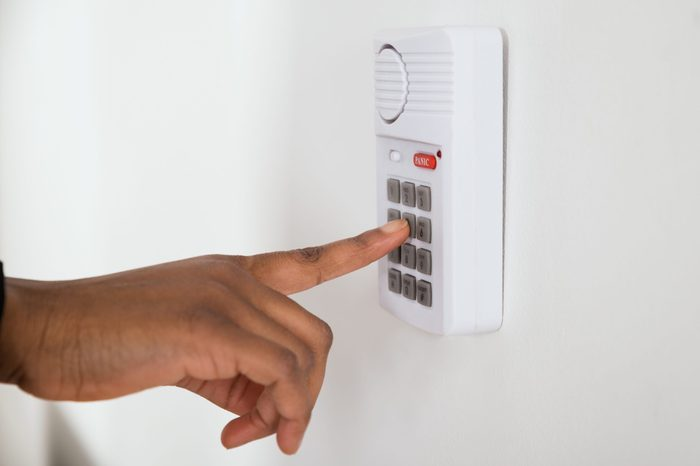 Close-up Of African Businesswoman Hand Pressing Button On Door Security System