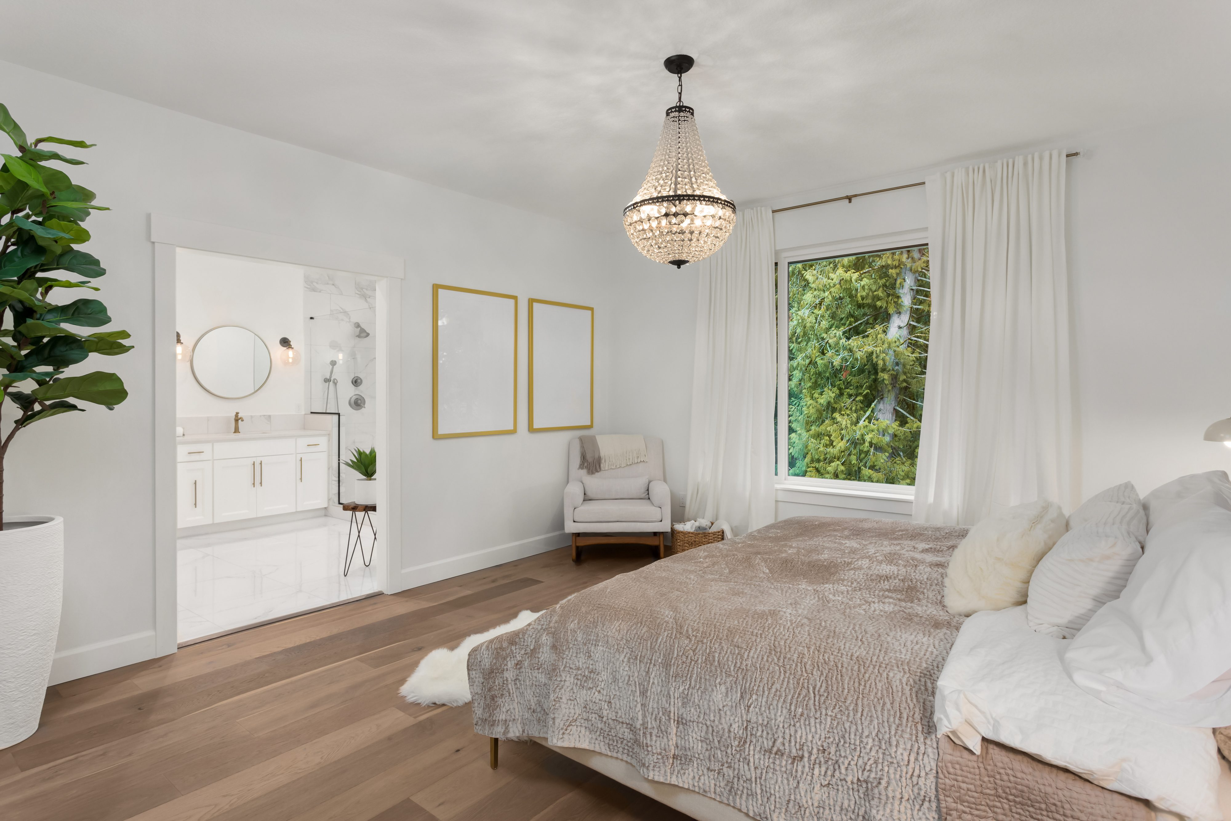 Beautiful Master Bedroom in New Luxury Home. Features Elegant Pendant Light, Hardwood Floors, and View of Ensuite Master Bathroom