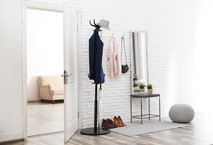 Stylish hallway interior with door and comfortable furniture
