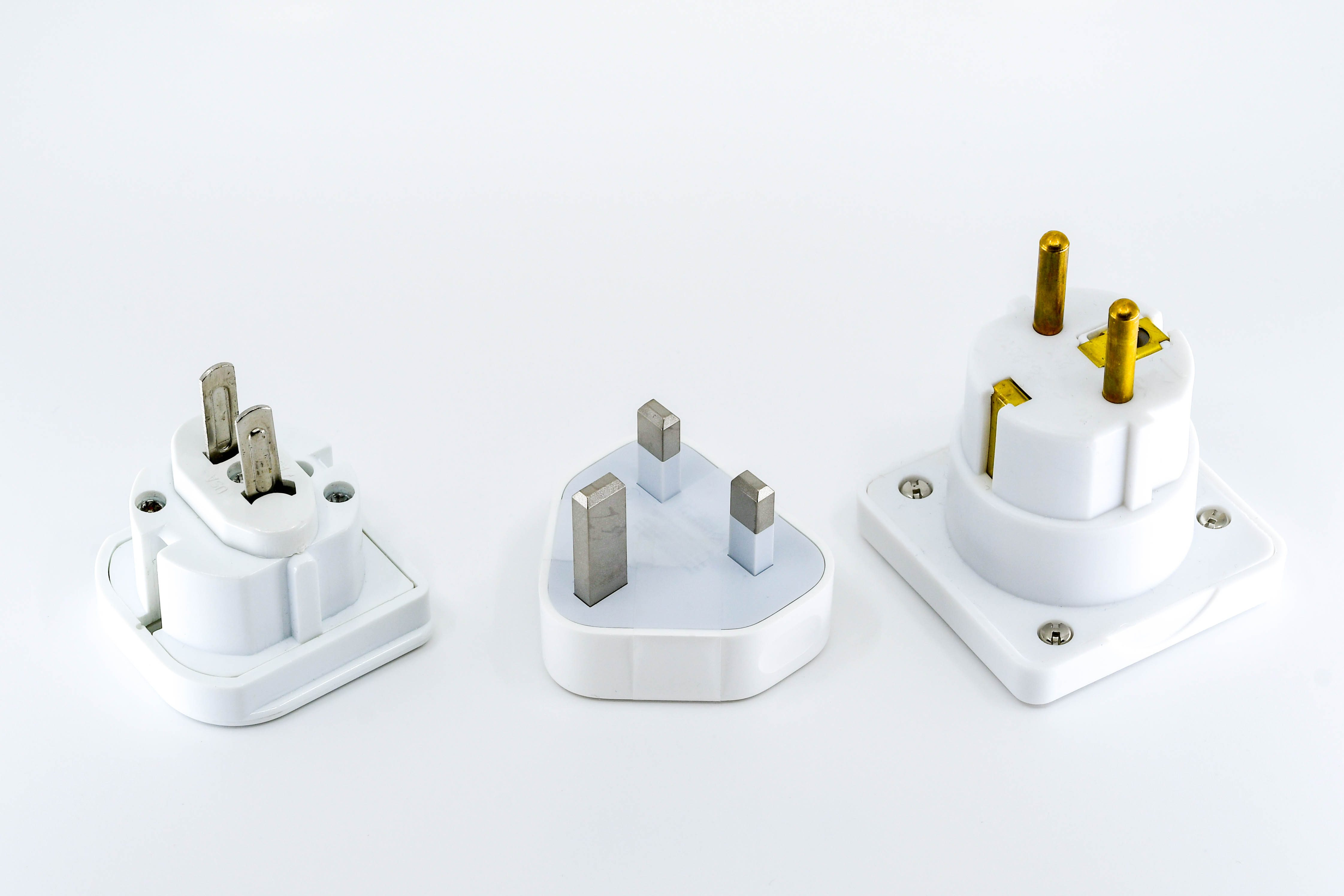Close up view of three different travel adapter plugs for mains power isolated against a plain white background. Left to right ar the adapters for the USA, UK and Europe.