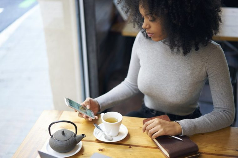 Skilled female afro American journalist chatting with chief editor finding out details for working task while waiting for workshop from food bloggers sitting in cafe using wireless internet and phone