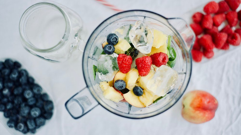 flat-lay of a blender and fresh seasonal berries and fruits over white background, cooking preparing smoothies, detox, healthy clean eating
