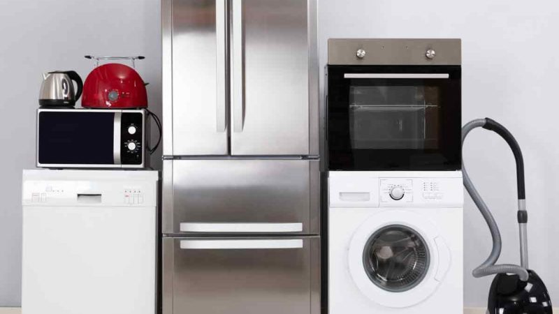 Close-up-Of-Home-Electronic-Appliances-On-Floor-Against-Grey-Wall-In-New-House