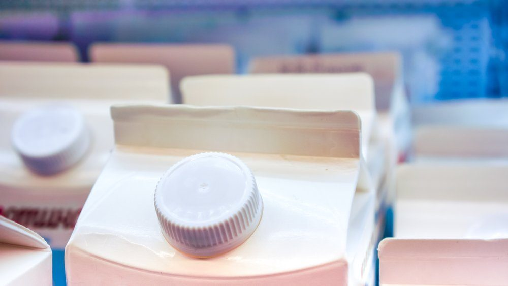 two long strong rows of milk in white carton packaging with round cap on the top stay at store shelf top side view.