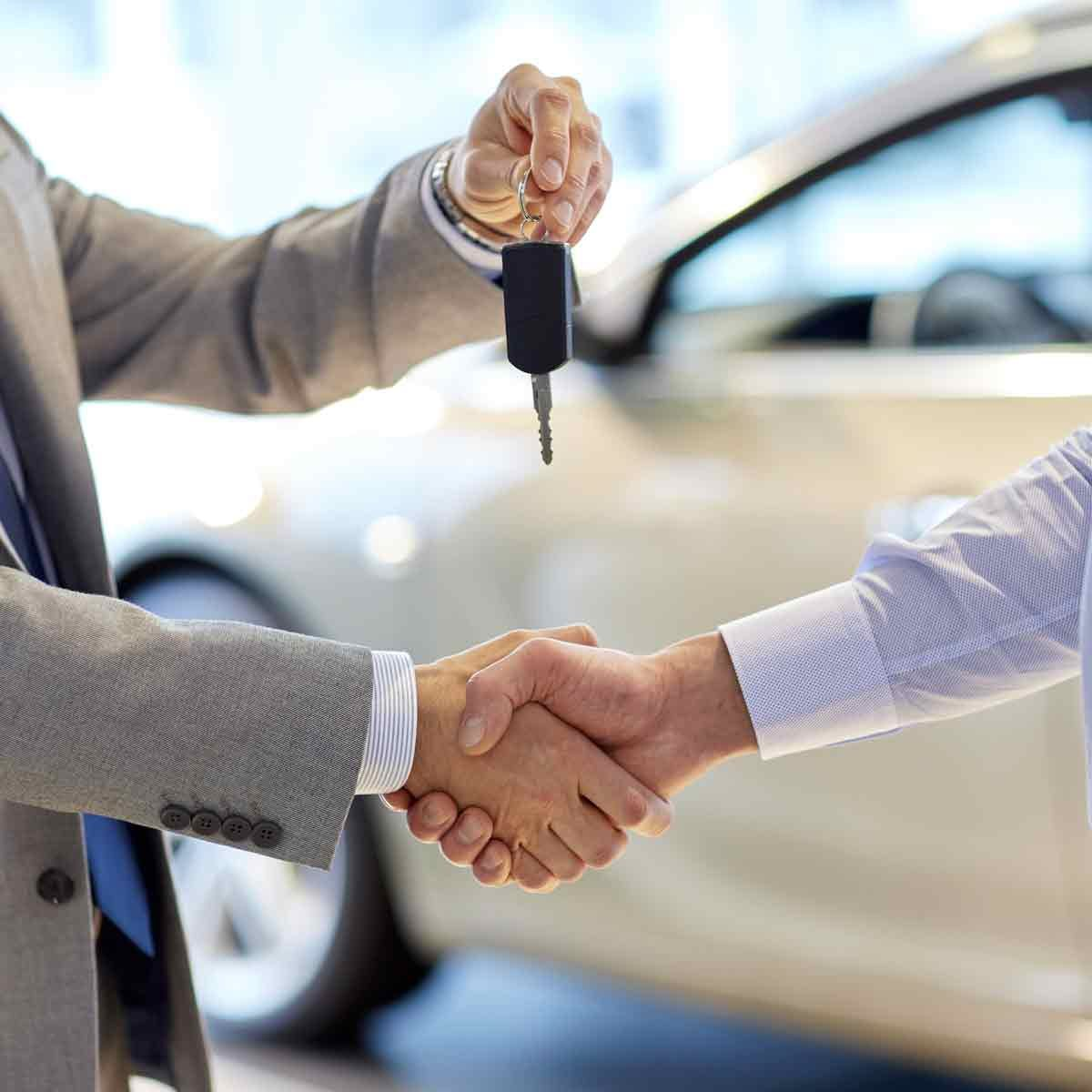 close-up-of-dealer-giving-key-to-new-owner-and-shaking-hands-in-auto-show