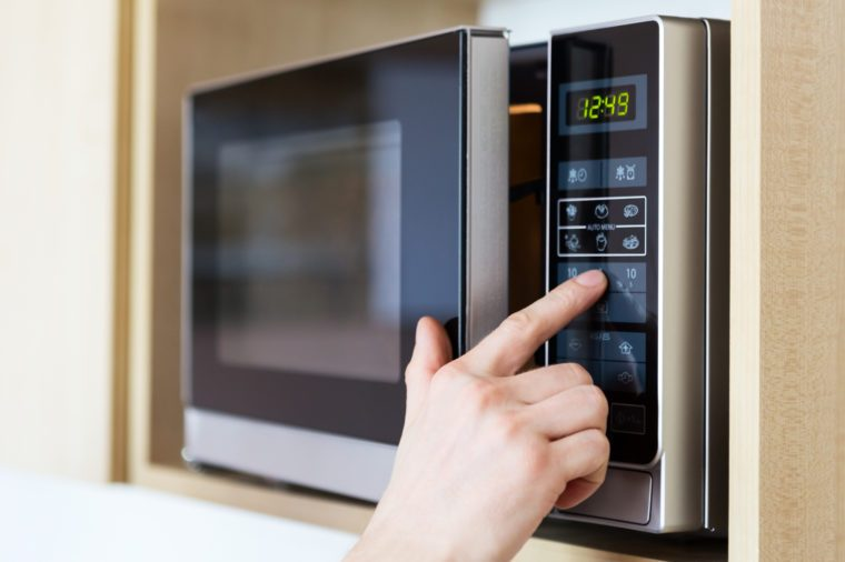 Detail of male hand while using the microwave