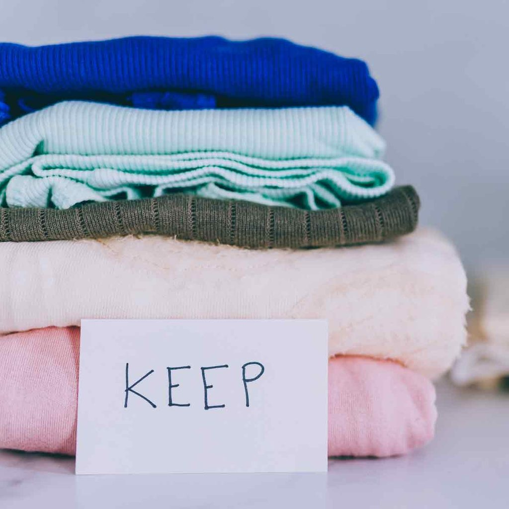 piles-of-tshirts-and-clothes-being-sorted-into-Keep-Discard-and-Donate-categories