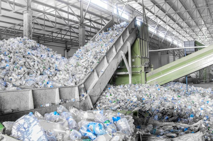 closeup escalator with a pile of plastic bottles at the factory for processing and recycling. PET recycling plant